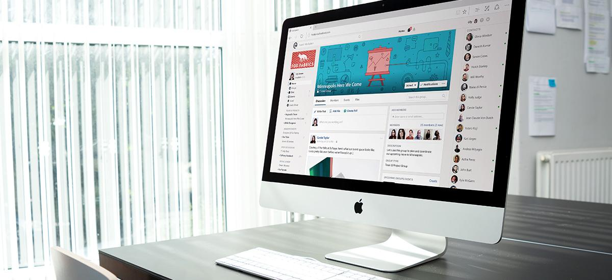 Desktop computer showing facebook workplace on screen